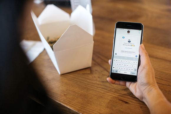 A table with food and woman's hand holding a smartphone with the Venmo app displayed.