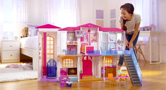 Girl playing with Barbie Dreamhouse