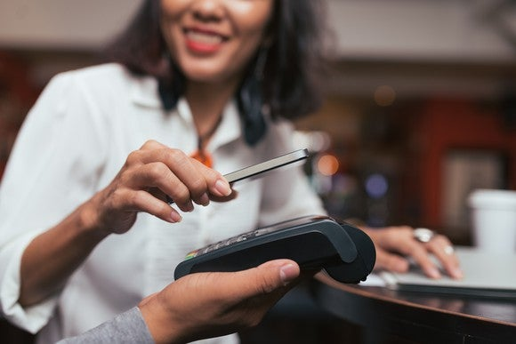 Woman using mobile phone to pay in a retail store.