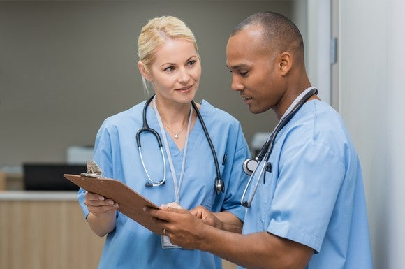 Man and woman in scrubs reviewing a chart