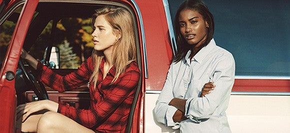 A pair of Abercrombie models pose inside and beside a pickup truck.