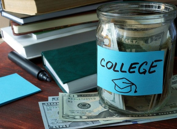 Glass jar with money that says college on top of more money and next to a pile of books