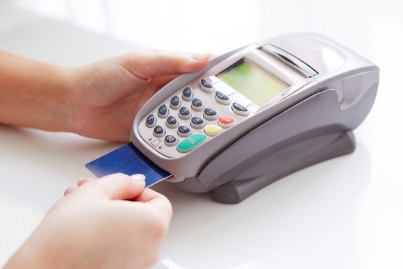 A credit card being processed at a check out counter.