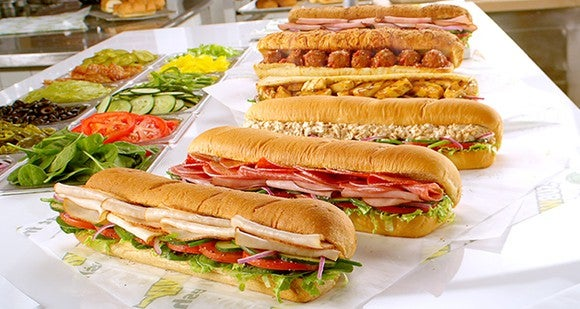 Six Subway sandwiches lined up on a countertop, with various vegetables displayed alongside.