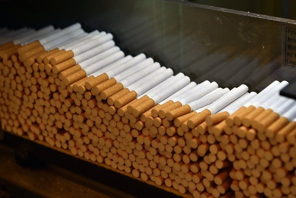 A pile of cigarettes being produced in a factory.