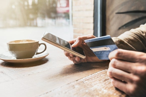 Person holding a credit card and a smartphone while sipping a latte.