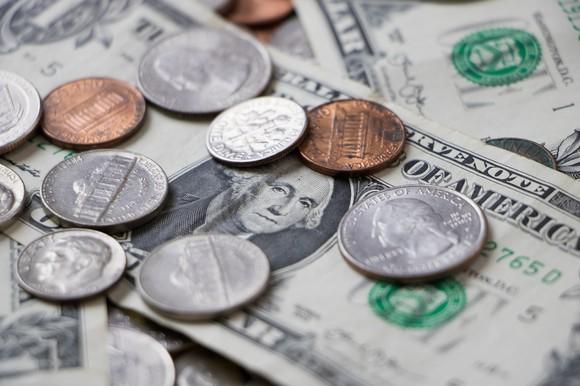 U.S. coins on top of $1 bills