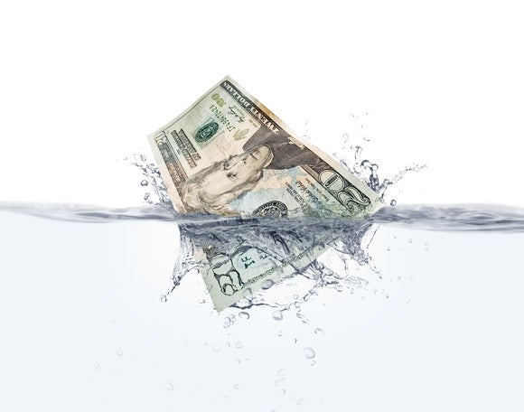 A twenty dollar bill splashing into the water.