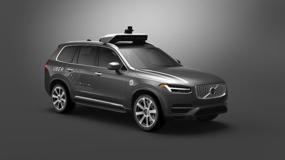 A gray Volvo XC90, a large crossover SUV, with Uber logos and visible self-driving sensor hardware.
