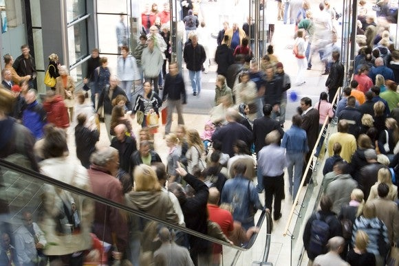Shoppers packed on a crowded escalator in a busy store.