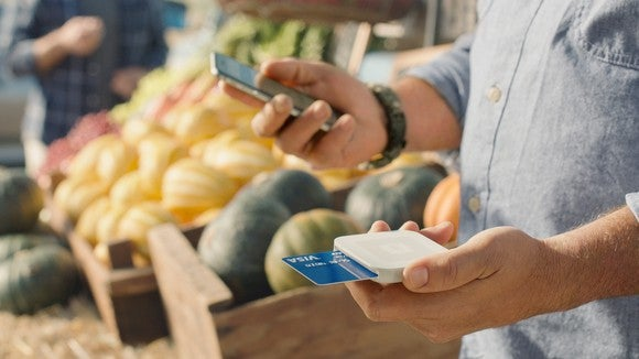 A man at a farmer's market holds a smartphone in one hand and a Square card reader, with credit card inserted, in another.