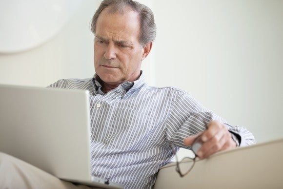An older man reads material on his laptop while sitting on a couch and holding his glasses in his hand.