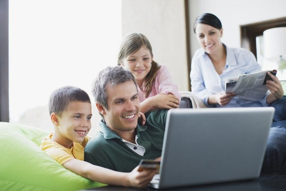 Family huddled around laptop looking at screen smiling.