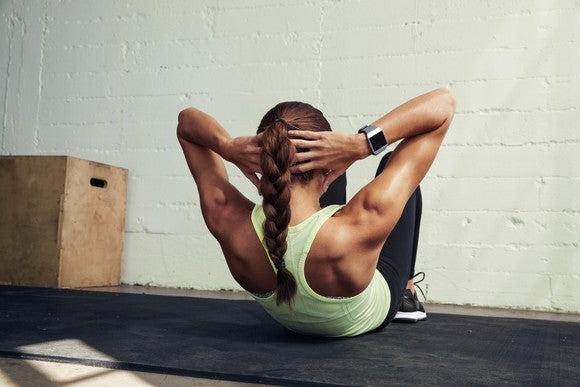 A woman doing a sit-up while wearing a Fitbit Ionic smartwatch and workout clothes.