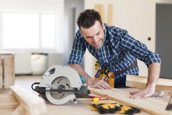 Handyman with tool belt working with wood using circular saw.