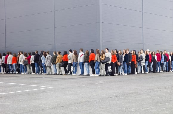 People waiting in line outside of a  store.