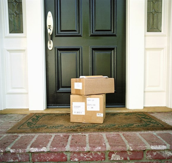 Stack of packages sitting on a front doorstep.
