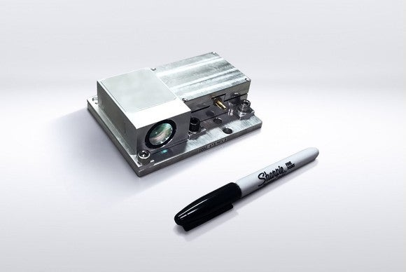 A Strobe lidar unit, a small metal box with a lens on the side, is shown next to a Sharpie marker. The Sharpie is a bit longer than the lidar unit.