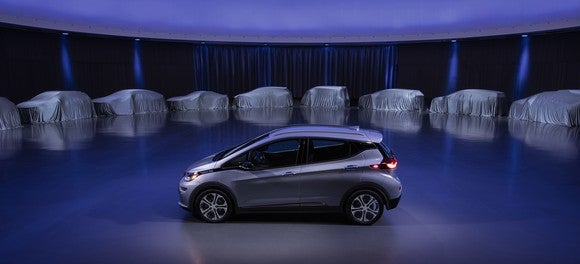 A silver Chevrolet Bolt EV on a stage, surrounded by 9 other vehicles hidden under white covers. GM said the covered vehicles represent some of its upcoming electric models.