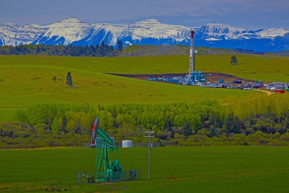 Drilling rig and pump jack with a mountain range in background.