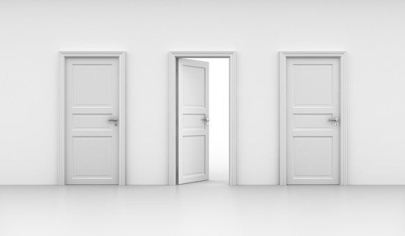 Three white doors with the middle door opened and the other two closed