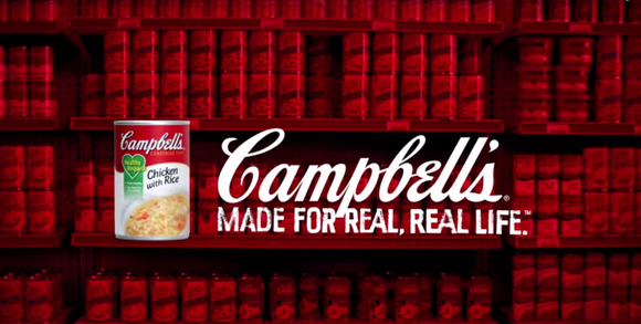 Bookshelf in background, can of Campbell Chicken with Rice in foreground with Campbell slogan.