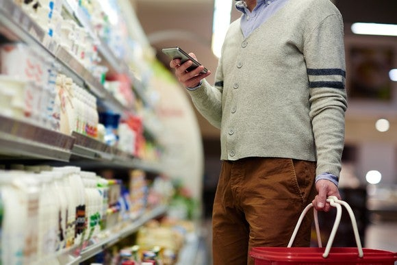 Man grocery shopping while looking at his smartphone.