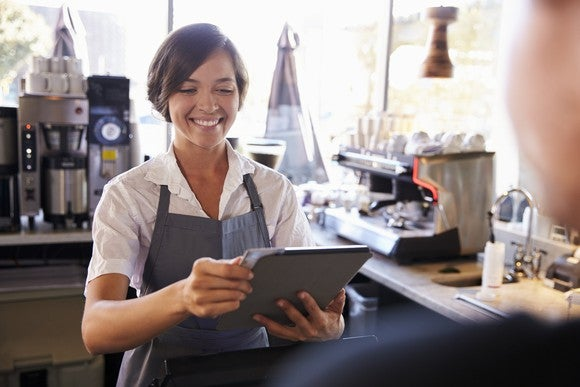 A smiling barista uses a tablet at point of sale.
