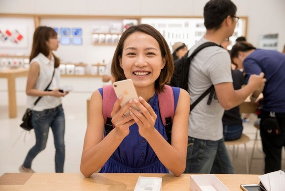 A woman holding a gold iPhone 8 at a wooden table inside of an Apple store.