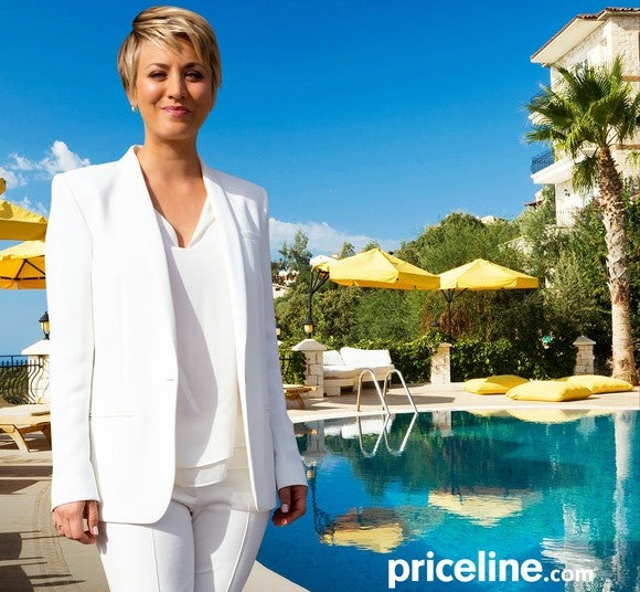 Priceline spokeswoman next to a swimming pool with palm trees and umbrella-covered tables.