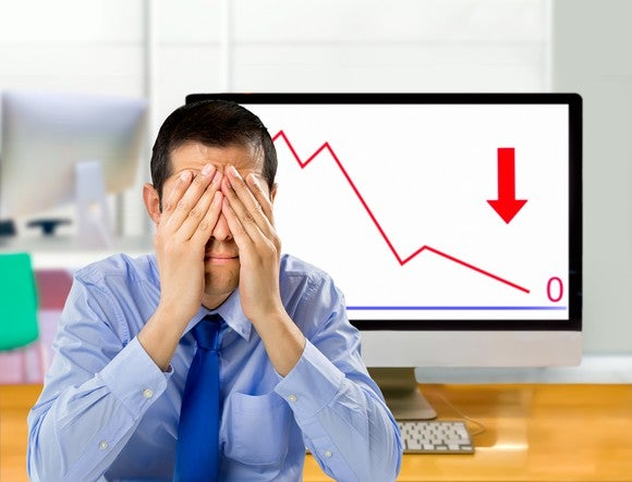 Man covering his face in front of a computer screen with a downward graph and an arrow pointed downward