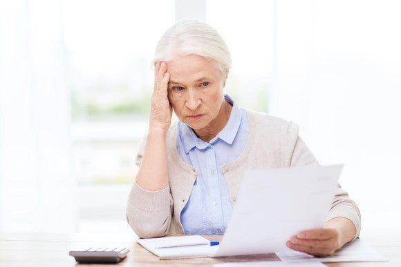 Senior woman holding her head while looking at a document