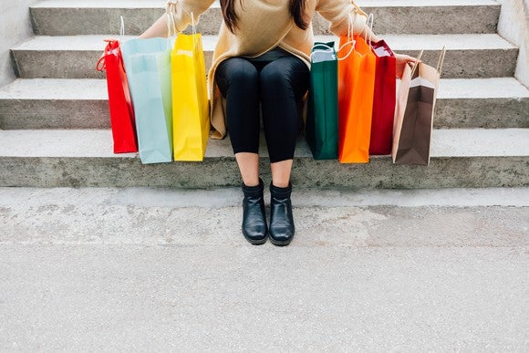 Someone sitting on concrete steps surrounded by shopping bags.