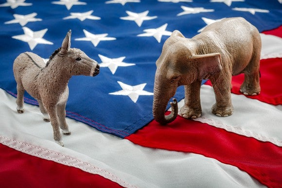 A Democrat donkey and Republican elephant squaring off while on top of the American flag.