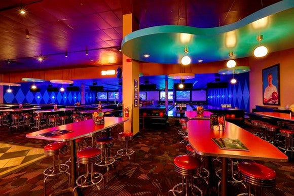 The interior of a Dave & Buster's, with a bowling alley in the background and bar stools and tables in the foreground.