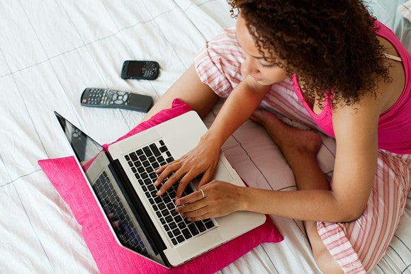 Overhead picture of a lady working on a laptop with two cellphones near by.