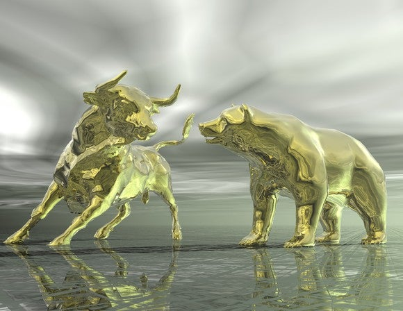 Golden bull and bear figures facing off on a windswept plain of silver.