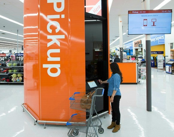 A woman with a shopping cart accesses an in-store Wal-Mart pickup tower.