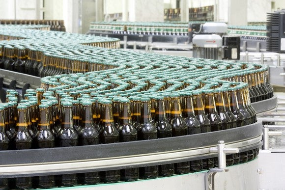 un-branded bottles on a conveyor belt in a bottling plant.