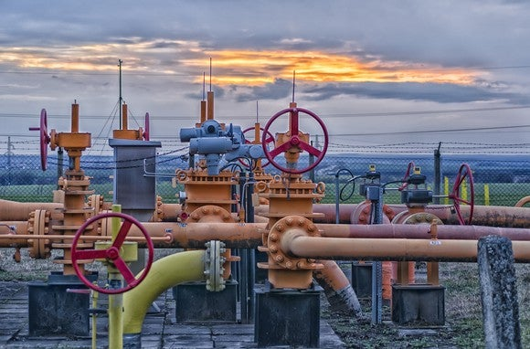 A natural gas field filled with pipelines and valves at sunset.