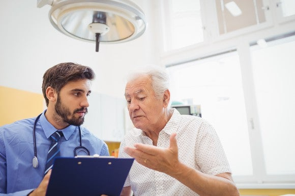 senior man talking to doctor holding clipboard medical expenses healthcare hospital