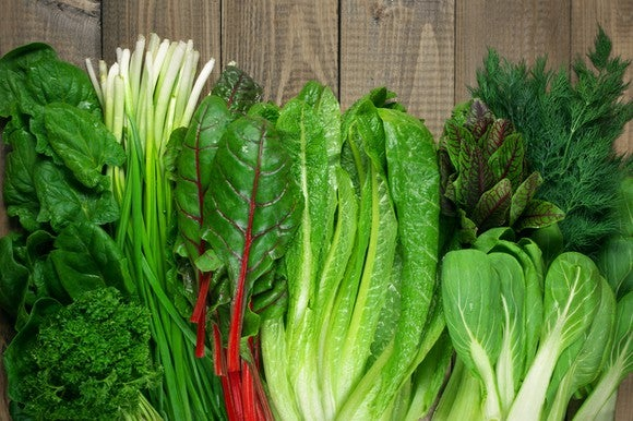 Leafy green vegetables on rustic wood table.