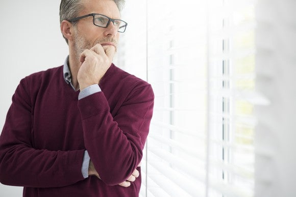 Businessman with hand on chin, deep in thought.