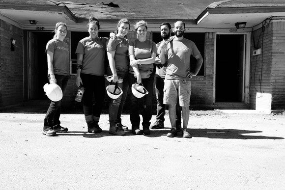 Six volunteers stand in front of a damaged house holding tools and construction helmets.