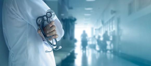 Medical professional in hospital hallway holding stethoscope.