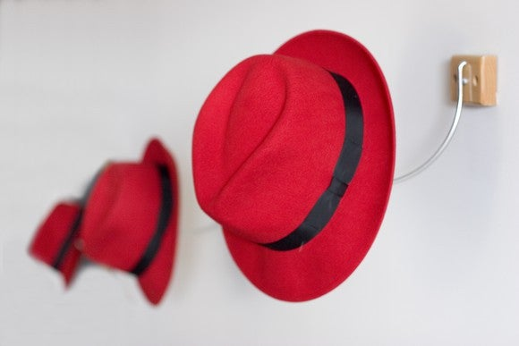 A row of red fedora hats hang on hooks.