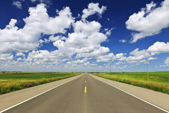 An open road and sky with puffy clouds