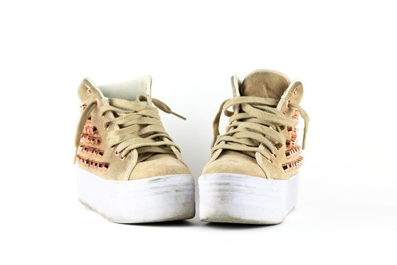 A pair of golden sneakers in a white room.