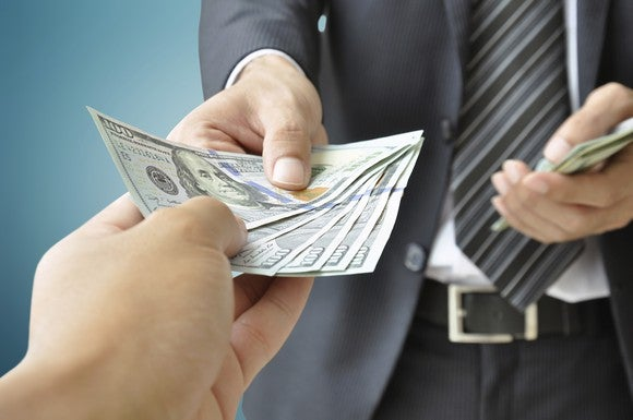 A businessman handing cash to an outstretched hand.