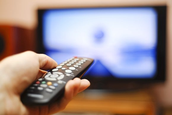 A hand points a remote at a TV.